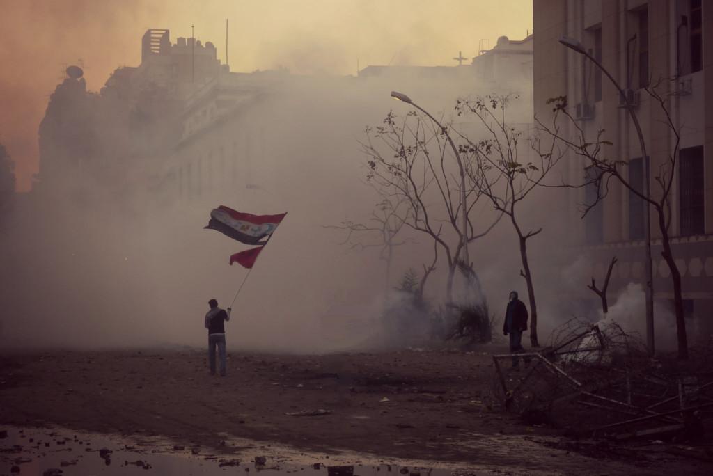 En 2012 en Égypte, ce manifestant brandissait le drapeau du pays ainsi que les emblèmes de l'islam et de la chrétienté, symbole de paix et d'œcuménisme. Crédit Alisdare Hickson.