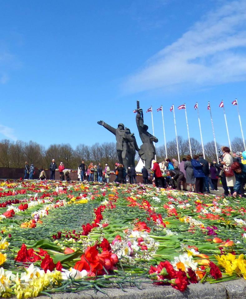 Au pied de la statut des libérateurs, on dépose des fleurs en hommage aux soldats tombés au combat. Crédit Elisa Maziere.