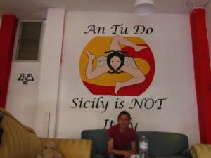"""Giorgio Martinico devant le tag """"Sicily is not Italy"""" du centre social autogéré Anomalia Crédits : Elsa Pécot"""