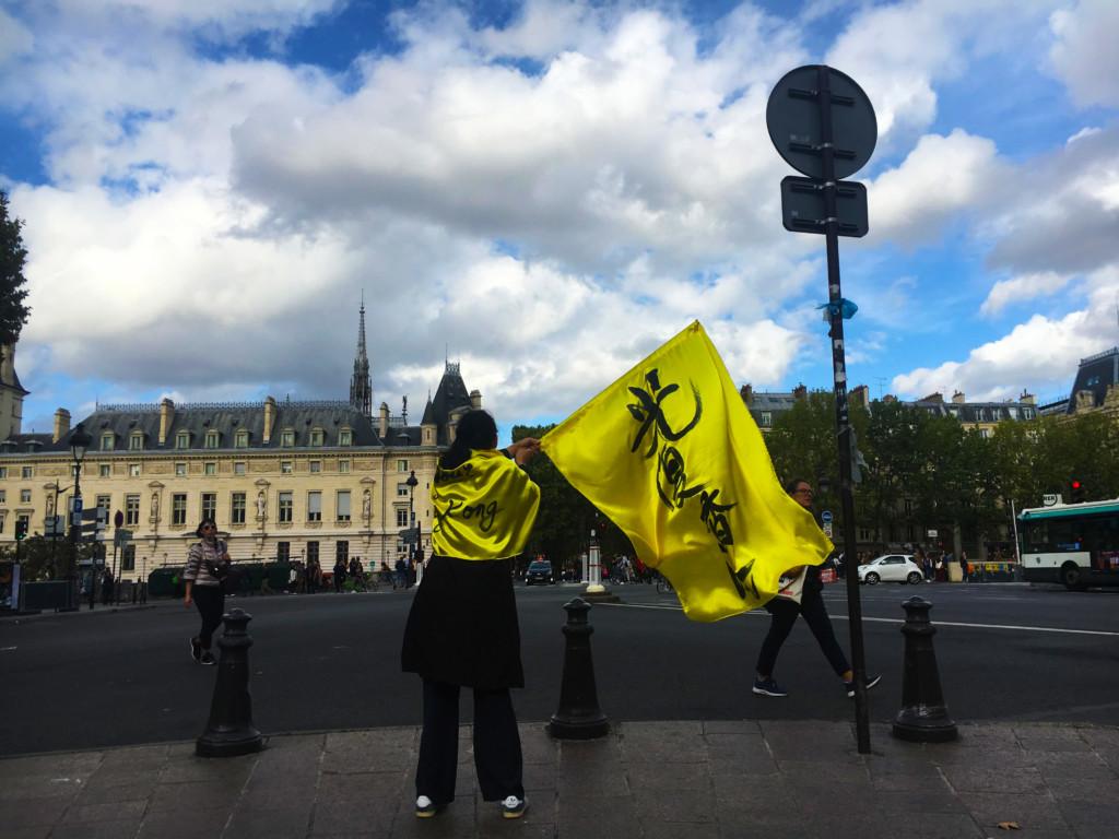 Une jeune femme tient un drapeau où l'on peut lire