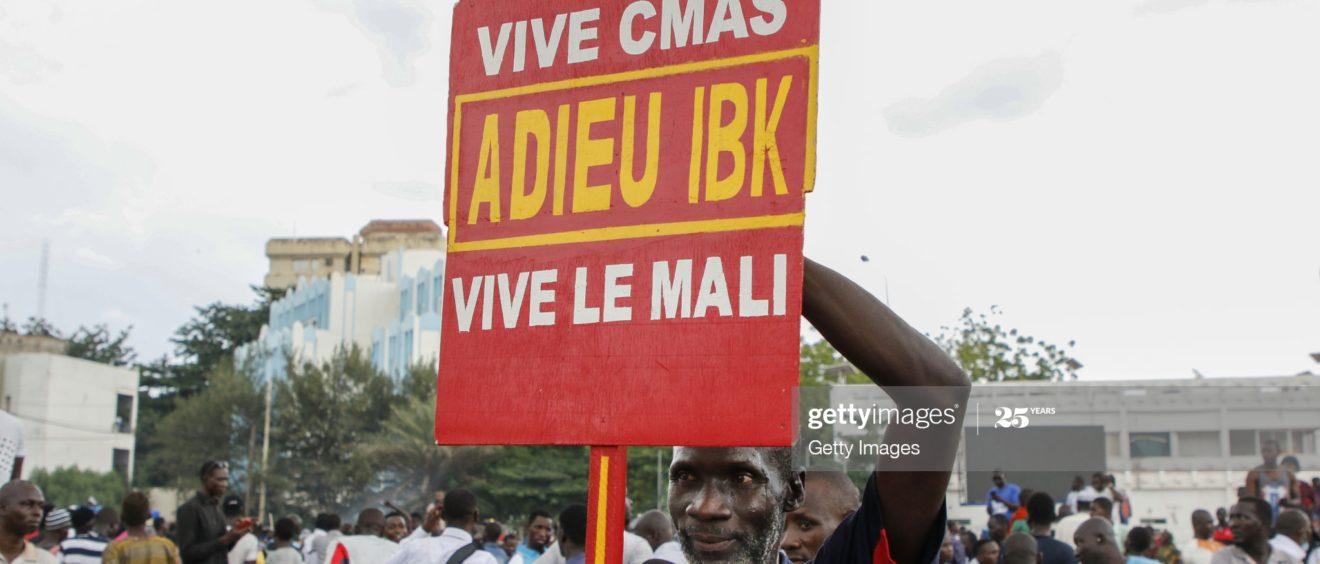 18 août 2020, homme malien tenant une pancarte en faveur d'une démission d'Ibrahim Boubacar Keita. Dans un même temps, les militaires paradent sur le Boulevard de l'Indépendance, après l'arrestation d'Ibrahim Boubacar Keita.