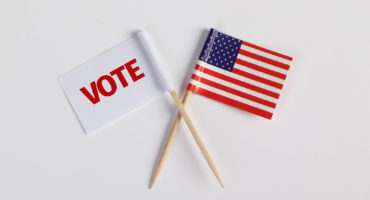 """Photo où l'on peut voir le drapeau des Etats-Unis ainsi qu'un autre drapeau où il y'a marqué """"Vote"""", afin d'encourager les Américains à voter"""